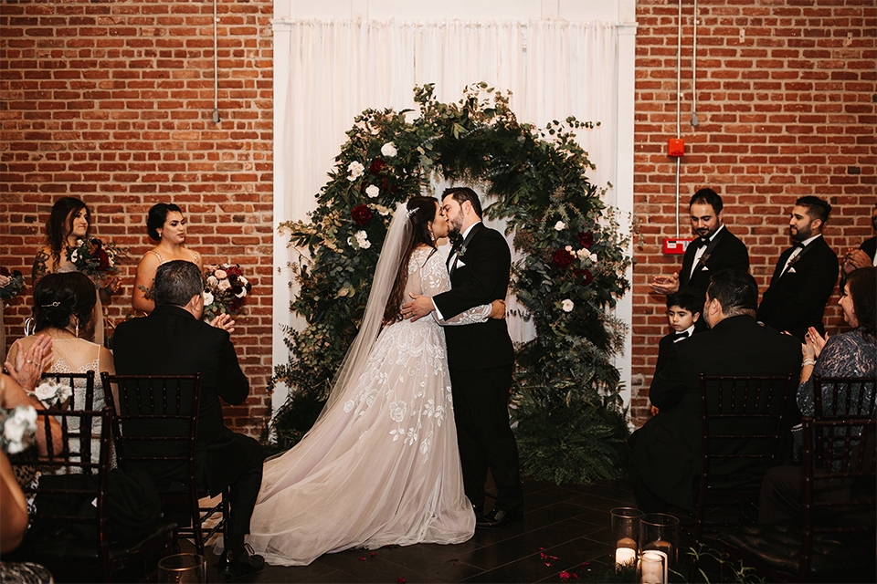 Orange county wedding at the estate on second bride lace ball gown with long sleeves and high neckline with crystal hair piece and groom black tuxedo with white dress shirt and black bow tie with white pocket square kissing during ceremony