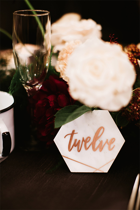 Orange county wedding at the estate on second dark brown wood table with gold place settings and white and green flower centerpiece decor with white glasses and candles and black chairs and white marble table numbers with gold calligraphy writing