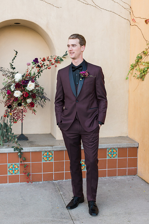 Los angeles valentine theme wedding shoot at the gardens at los robles groom burgundy tuxedo with black dress shirt and black bow tie with red floral boutonniere standing with hands in pockets