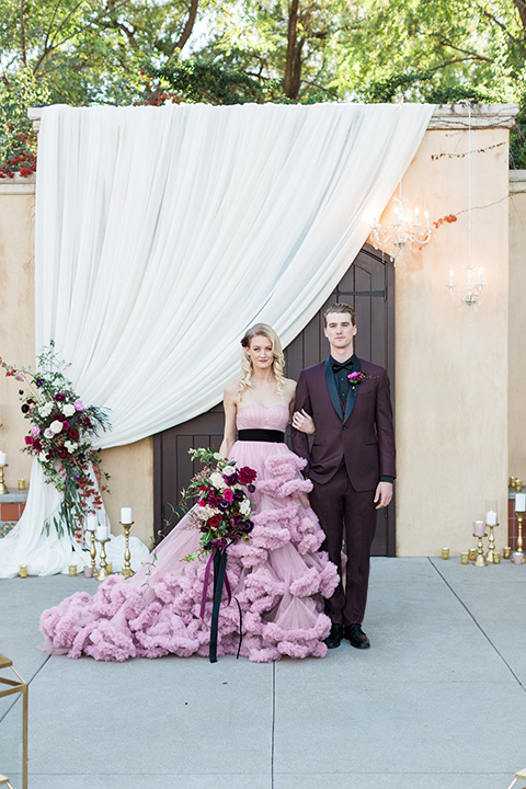 Los angeles valentine theme wedding shoot at the gardens at los robles bride pink ballgown dress with ruffled skirt and dark pink and white floral bridal bouquet with groom burgundy tuxedo with black dress shirt and black bow tie with red floral boutonniere