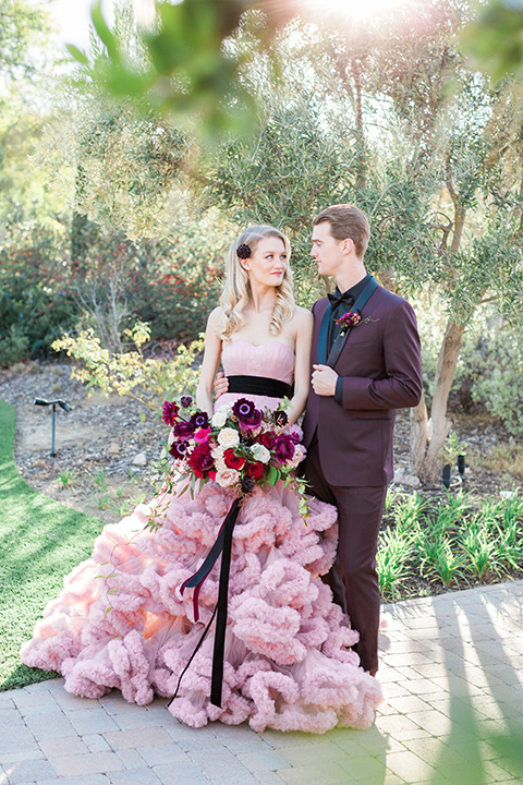 Los angeles valentine theme wedding shoot at the gardens at los robles bride pink ballgown dress with ruffled skirt and dark pink and white floral bridal bouquet with groom burgundy tuxedo with black dress shirt and black bow tie with red floral boutonniere walking and holding hands