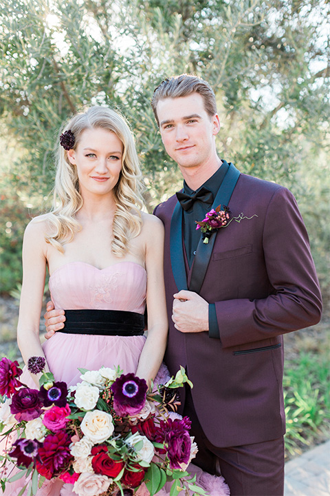 Los angeles valentine theme wedding shoot at the gardens at los robles bride pink ballgown dress with ruffled skirt and dark pink and white floral bridal bouquet with groom burgundy tuxedo with black dress shirt and black bow tie with red floral boutonniere smiling
