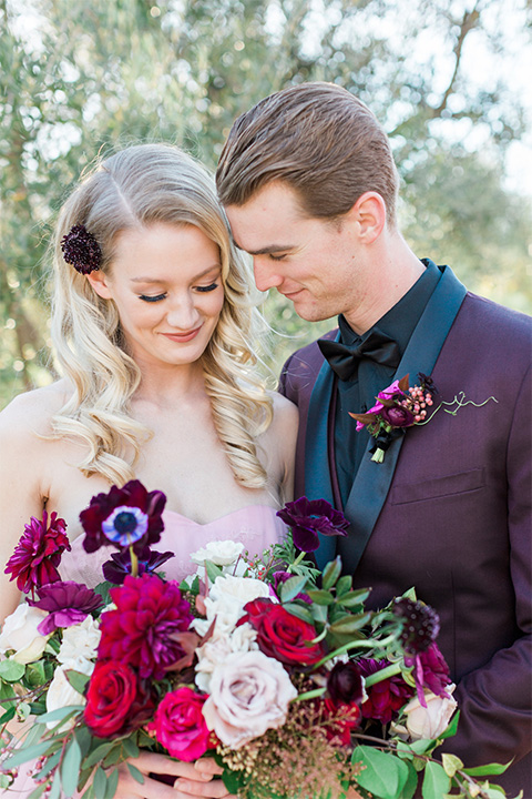 Los angeles valentine theme wedding shoot at the gardens at los robles bride pink ballgown dress with ruffled skirt and dark pink and white floral bridal bouquet with groom burgundy tuxedo with black dress shirt and black bow tie with red floral boutonniere smiling close up