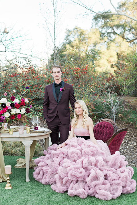 Los angeles valentine theme wedding shoot at the gardens at los robles bride pink ballgown dress with ruffled skirt and dark pink and white floral bridal bouquet with groom burgundy tuxedo with black dress shirt and black bow tie with red floral boutonniere sitting in vintage lounge furniture