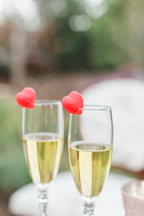 Los angeles valentine theme wedding shoot at the gardens at los robles vintage red and white lounge furniture with table and flower deocr and white and gold place settings with gold silverware with champagne glasses and heart decor