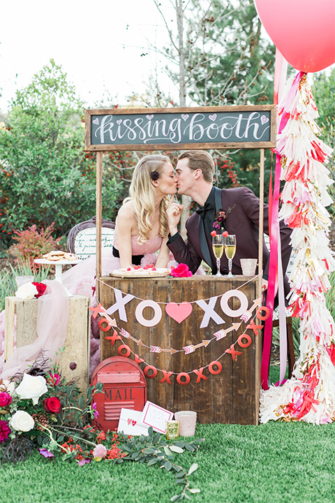 Los angeles valentine theme wedding shoot at the gardens at los robles bride pink ballgown dress with ruffled skirt and dark pink and white floral bridal bouquet with groom burgundy tuxedo with black dress shirt and black bow tie with red floral boutonniere kissing in kissing booth