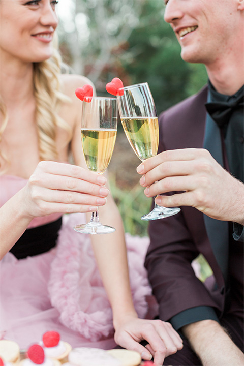 Los angeles valentine theme wedding shoot at the gardens at los robles bride pink ballgown dress with ruffled skirt and dark pink and white floral bridal bouquet with groom burgundy tuxedo with black dress shirt and black bow tie with red floral boutonniere holding champagne glasses