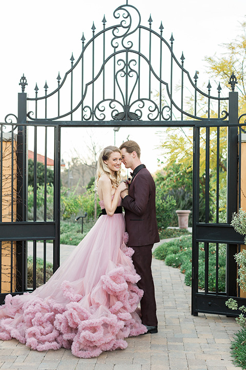 Los angeles valentine theme wedding shoot at the gardens at los robles bride pink ballgown dress with ruffled skirt and dark pink and white floral bridal bouquet with groom burgundy tuxedo with black dress shirt and black bow tie with red floral boutonniere hugging