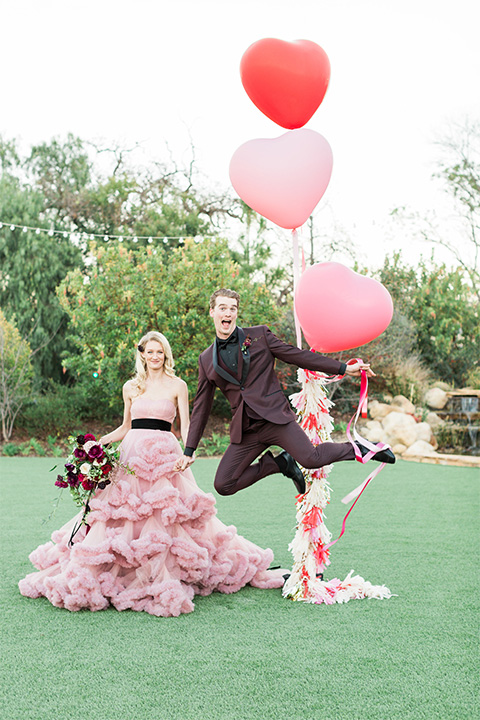 Los angeles valentine theme wedding shoot at the gardens at los robles bride pink ballgown dress with ruffled skirt and dark pink and white floral bridal bouquet with groom burgundy tuxedo with black dress shirt and black bow tie with red floral boutonniere holding balloons and groom jumping