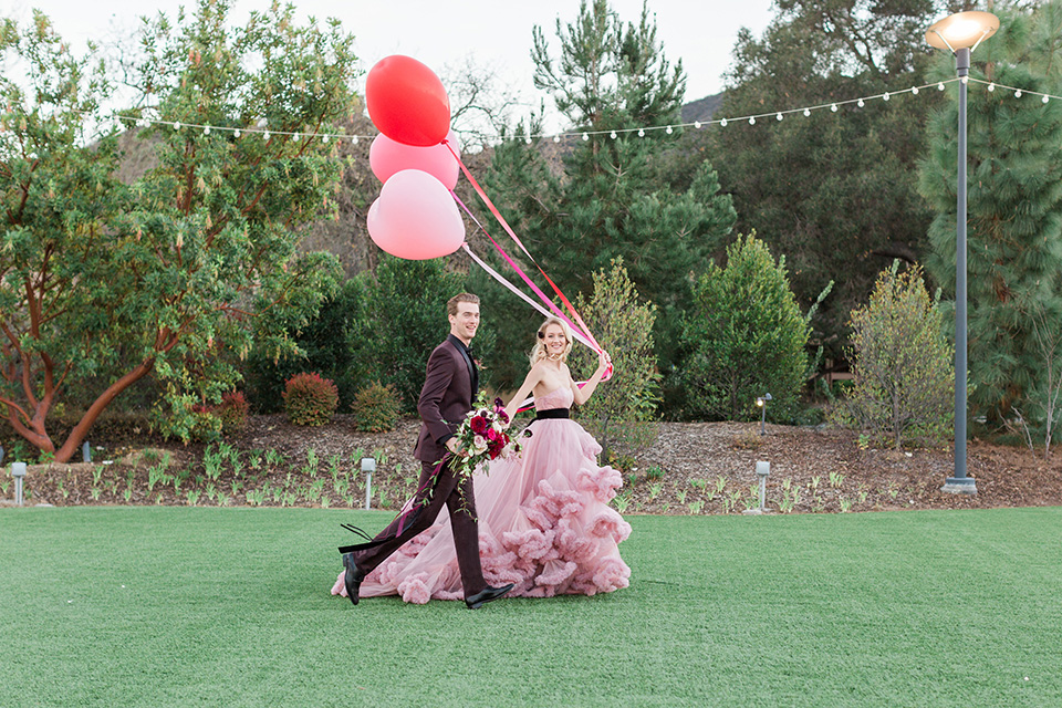 Los angeles valentine theme wedding shoot at the gardens at los robles bride pink ballgown dress with ruffled skirt and dark pink and white floral bridal bouquet with groom burgundy tuxedo with black dress shirt and black bow tie with red floral boutonniere walking and holding balloons
