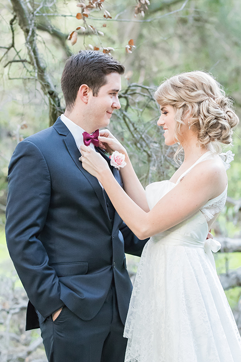 Valentine styled wedding shoot bride chiffon gown with halter straps and sweetheart neckline with groom navy blue suit with notch lapel with matching vest and white dress shirt with red bow tie and white floral boutonniere hugging