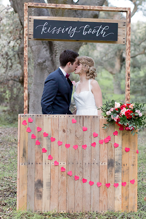 Valentine styled wedding shoot bride chiffon gown with halter straps and sweetheart neckline with groom navy blue suit with notch lapel with matching vest and white dress shirt with red bow tie and white floral boutonniere kissing in kissing booth