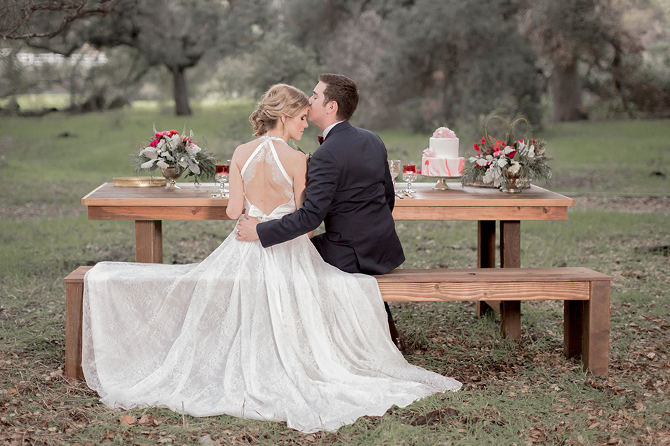 Valentine styled wedding shoot bride chiffon gown with halter straps and sweetheart neckline with groom navy blue suit with notch lapel with matching vest and white dress shirt with red bow tie and white floral boutonniere sitting at table kissing