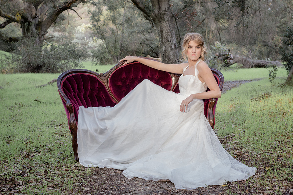 Valentine styled wedding shoot bride chiffon gown with halter straps and sweetheart neckline holding red and pink floral bridal bouquet sitting on red vintage couch