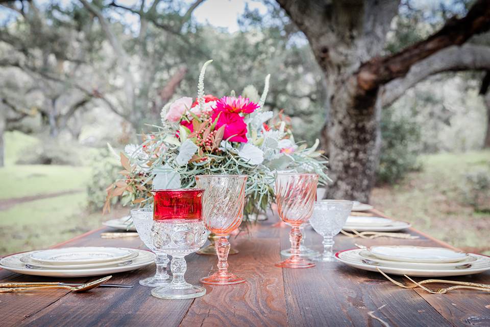 Valentine styled wedding shoot table set up dark brown wood table with pink flower centerpiece decor with pink and white place settings with red wine glasses and gold silverware