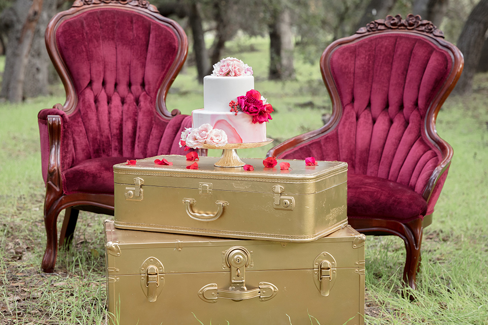 Valentine styled wedding shoot table set up dark brown wood table with pink flower centerpiece decor with pink and white place settings with red wine glasses and gold silverware with pink and white wedding cake on gold vintage suitcase decor
