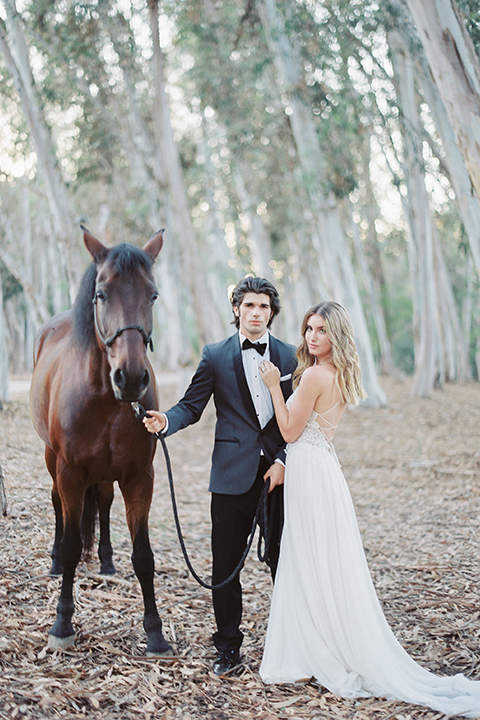 Into the woods outdoor romantic wedding shoot bride chiffon gown with thin spahetti straps and strap design on back with lace detail and sweetheart neckline with groom charcoal grey tuxedo coat with black lapels and black pants with white dress shirt and black bow tie with horse