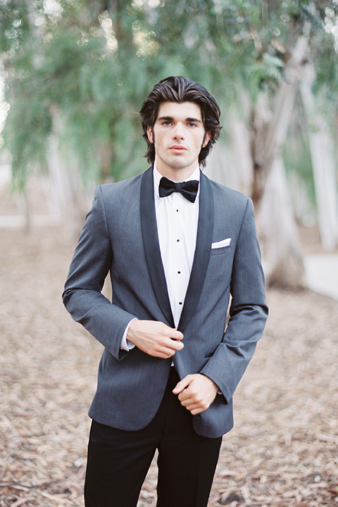 Into the woods outdoor romantic wedding shoot groom charcoal grey tuxedo with black lapels and black pants with white dress shirt and black bow tie with white pocket square holding jacket