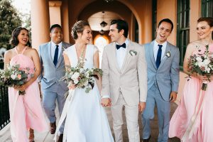 San diego big fake wedding shoot bride a line chiffon gown with plunging neckline and lace detail on back with short sleeves with groom tan suit with matching vest and white dress shirt with navy blue bow tie and white floral boutonniere with bridesmaids long pink dresses and groomsmen light blue suits walking