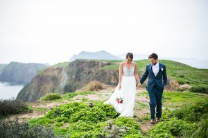 Channel islands wedding shoot bride ball gown with lace bodice and thin straps with plunging neckline and open back design with groom blue suit with matching vest and white dress shirt with long silver striped tie and pink and white floral boutonniere holding hands