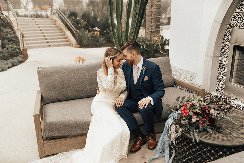 Dana point outdoor wedding shoot at monarch beach resort bride form fitting lace gown with long sleeves and high neckline with groom navy blue suit with matching vest and white dress shirt with long blush pink striped tie and matching pocket square sitting on couch