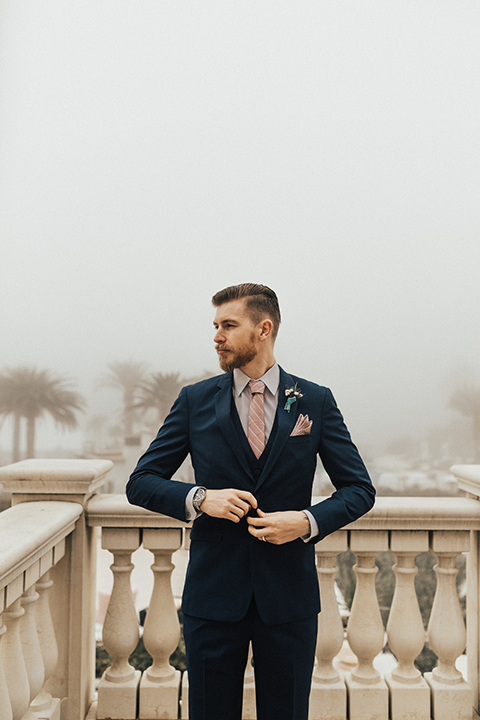 Dana point outdoor wedding shoot at monarch beach resort groom navy blue suit with matching vest and long blush pink striped tie and matching pocket square with floral boutonniere