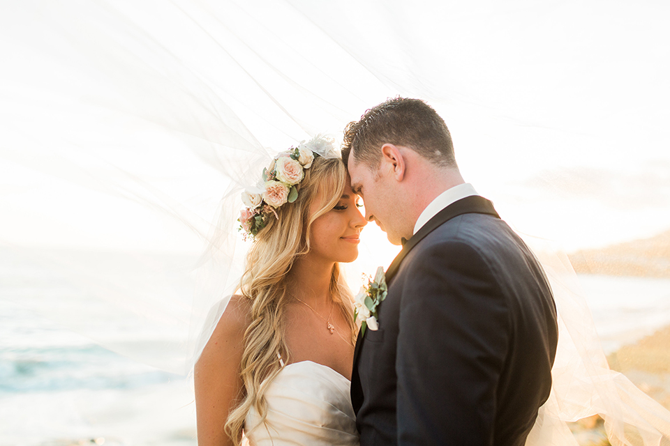 Laguna beach wedding bride ball gown with thin spaghetti straps and a sweetheart neckline with groom navy blue tuxedo with black shawl lapel and white dress shirt with black bow tie and white floral boutonniere hugging