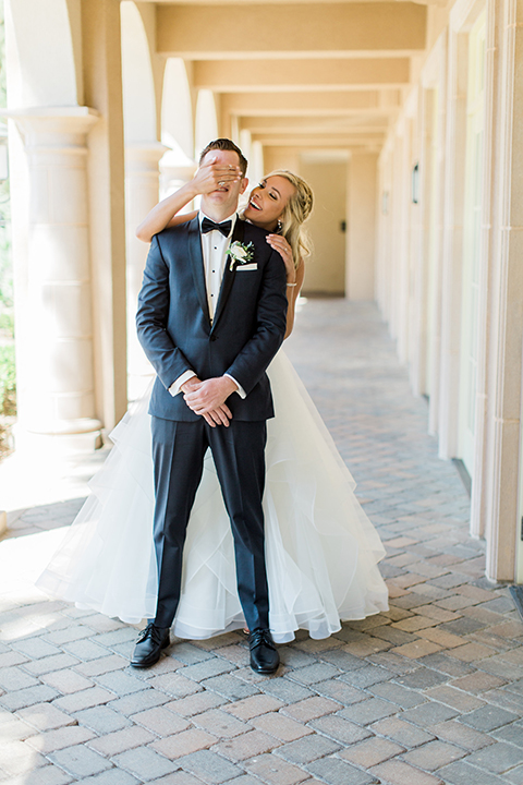 Laguna beach wedding bride ball gown with thin spaghetti straps and a sweetheart neckline with groom navy blue tuxedo with black shawl lapel and white dress shirt with black bow tie and white floral boutonniere bride behind groom covering eyes for first look
