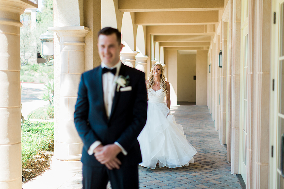Laguna beach wedding bride ball gown with thin spaghetti straps and a sweetheart neckline with groom navy blue tuxedo with black shawl lapel and white dress shirt with black bow tie and white floral boutonniere bride walking behind groom for first look