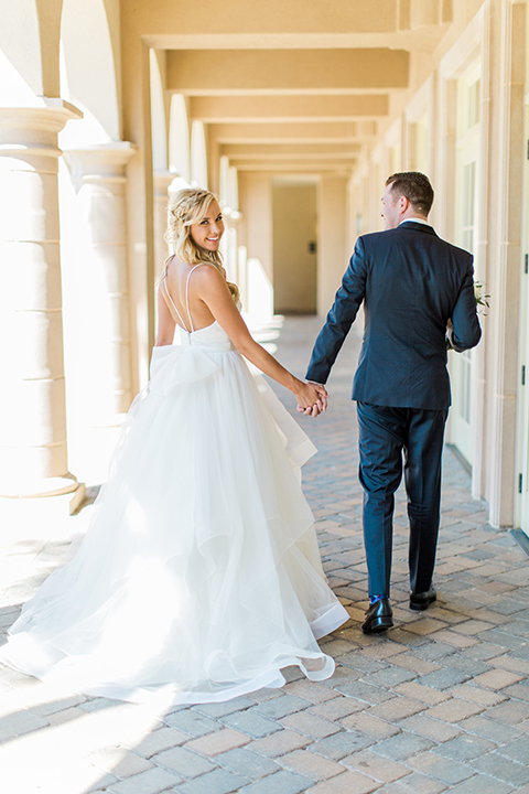 Laguna beach wedding bride ball gown with thin spaghetti straps and a sweetheart neckline with groom navy blue tuxedo with black shawl lapel and white dress shirt with black bow tie and white floral boutonniere holding hands after first