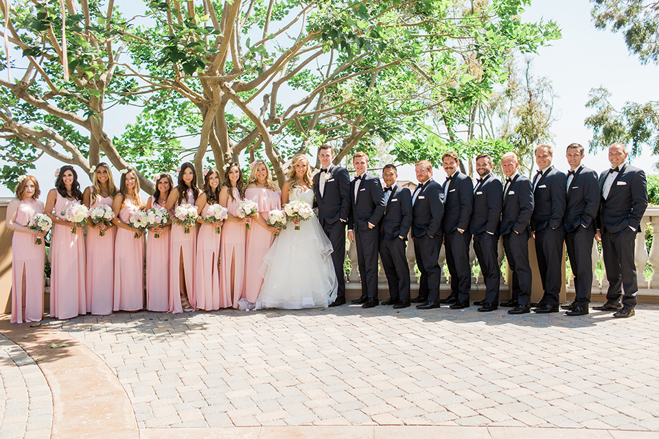 Laguna beach wedding bride ball gown with thin spaghetti straps and a sweetheart neckline with groom navy blue tuxedo with black shawl lapel and white dress shirt with black bow tie and white floral boutonniere with bridesmaids long blush pink dresses with groomsmen navy blue tuxedos and black bow ties