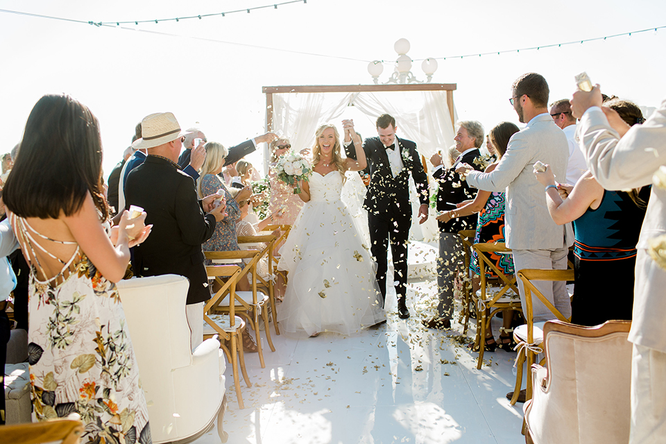 Laguna beach wedding bride ball gown with thin spaghetti straps and a sweetheart neckline with groom navy blue tuxedo with black shawl lapel and white dress shirt with black bow tie and white floral boutonniere walking down the aisle after ceremony with white flower petals
