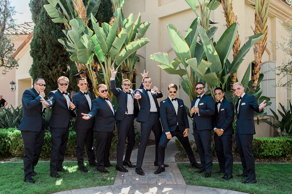 Laguna beach wedding groom navy blue tuxedo with a black shawl lapel and white dress shirt with black bow tie and white pocket square with white floral boutonniere with groomsmen navy blue tuxedos with black bow ties and white floral boutonnieres