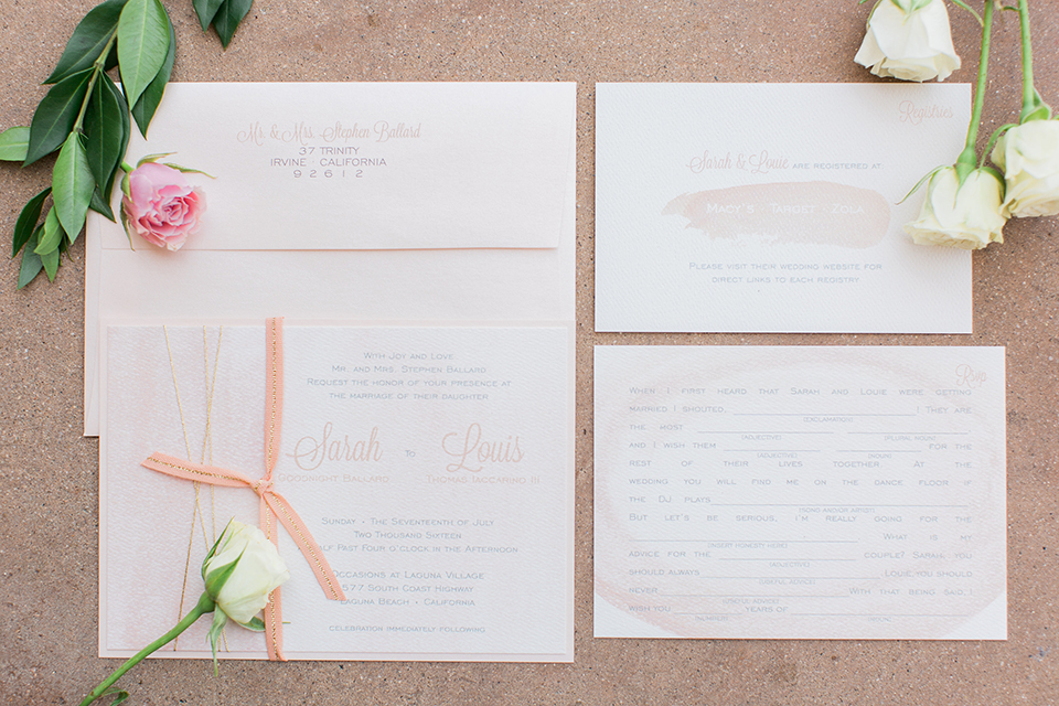 Laguna beach wedding white wedding invitations with pink and white flowers on sand wedding photo idea for invitations layed out on ground