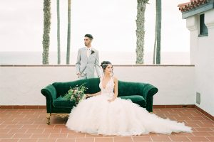 Orange county wedding shoot at ole hanson beach club bride ball gown with lace bodice and straps with plunging neckline halter design with crystal headpiece and groom light grey suit with matching vest and white dress shirt with long ivory tie with white and purple floral boutonniere sitting on couch