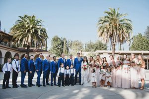 Orange county wedding at the colony house bride long sleeve lace gown with big sleeves and plunging neckline with sheer details with groom cobalt blue suit with matching vest and white dress shirt with long black skinny tie and white floral boutonniere with bridesmaids long blush pink dresses with groomsmen cobalt blue suits with long black skinny ties