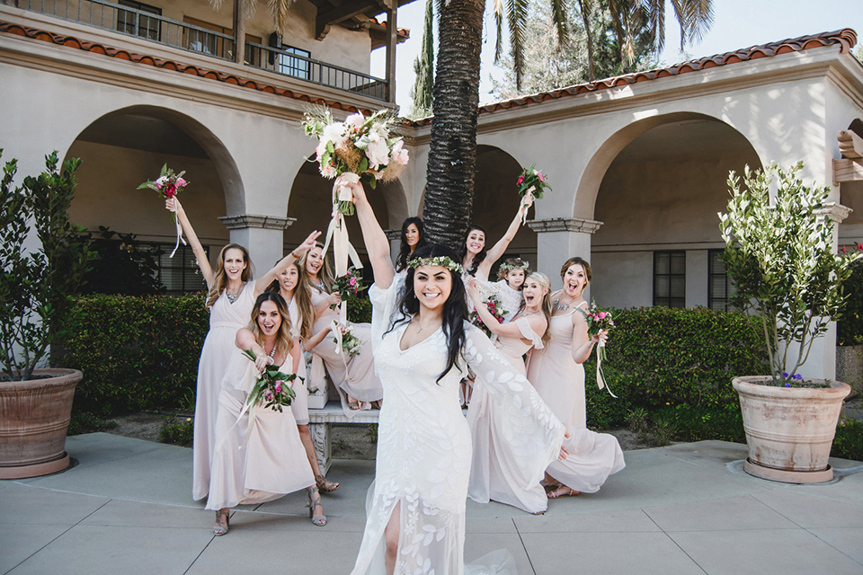 Orange county wedding at the colony house bride long sleeve lace gown with big sleeves and plunging neckline with sheer details with bridesmaids long blush pink dresses with white and pink floral bridal bouquets cheering