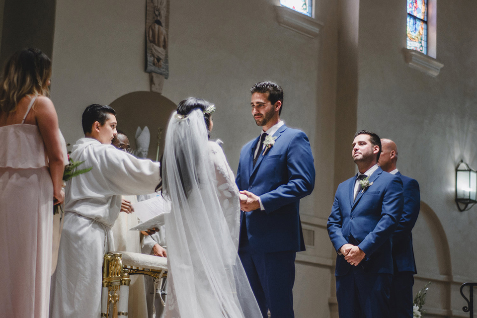 Orange county wedding at the colony house bride long sleeve lace gown with big sleeves and plunging neckline with sheer details with groom cobalt blue suit with matching vest and white dress shirt with long black skinny tie and white floral boutonniere holding hands during ceremony