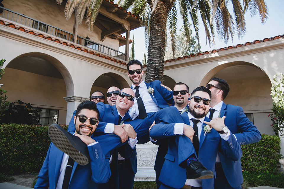 Orange county wedding at the colony house groom cobalt blue suit with matching vest and white dress shirt with long black skinny tie and white floral boutonniere being carried by groomsmen cobalt blue suits with matching vests and white dress shirts with long black skinny ties