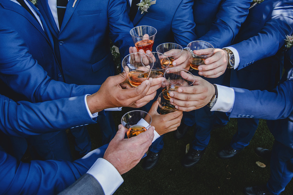 Orange county wedding at the colony house groom cobalt blue suit with matching vest and white dress shirt with long black skinny tie and white floral boutonniere toasting drinks with groomsmen cobalt blue suits with matching vests and white dress shirts and long black ties