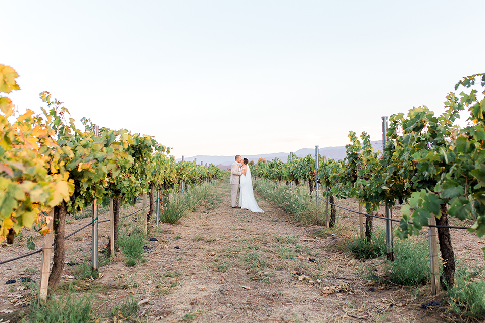 Temecula outdoor wedding at ponte winery bride form fitting lace gown with long sleeves and illusion open back design with sweetheart neckline and groom tan suit with matching vest and white dress shirt with matching tan bow tie and white floral boutonniere walking in vineyard