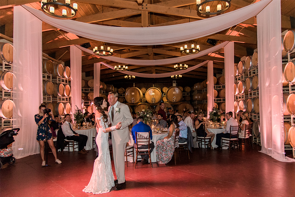 Temecula outdoor wedding at ponte winery bride form fitting lace gown with long sleeves and illusion open back design with sweetheart neckline and groom tan suit with matching vest and white dress shirt with matching tan bow tie and white floral boutonniere first dance during reception