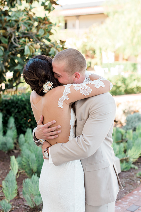 Temecula outdoor wedding at ponte winery bride form fitting lace gown with long sleeves and illusion open back design with sweetheart neckline and groom tan suit with matching vest and white dress shirt with matching tan bow tie and white floral boutonniere hugging after first look