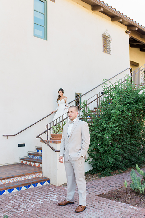 Temecula outdoor wedding at ponte winery bride form fitting lace gown with long sleeves and illusion open back design with sweetheart neckline and groom tan suit with matching vest and white dress shirt with matching tan bow tie and white floral boutonniere bride walking down the stairs for first look
