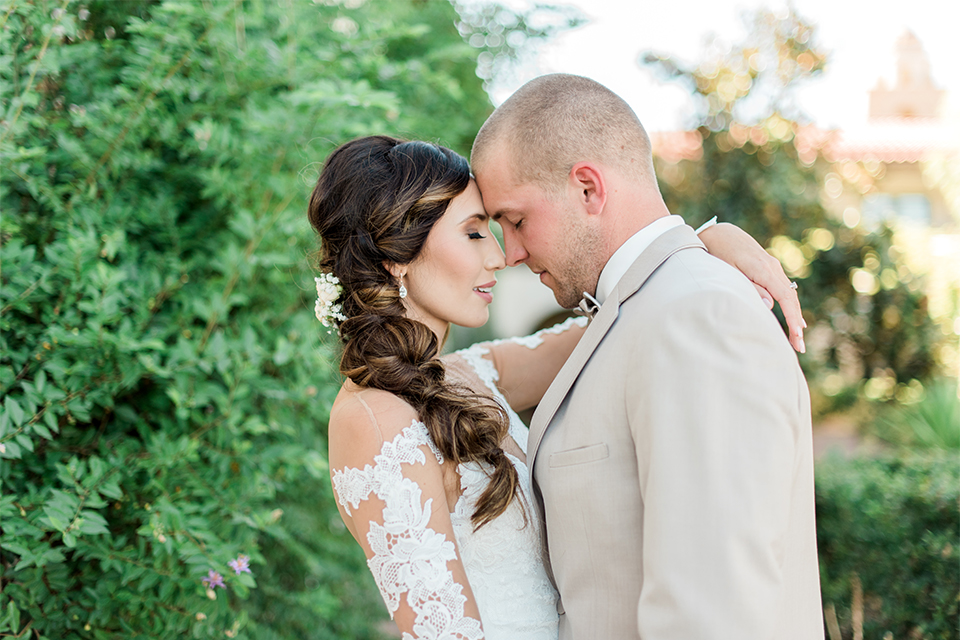 Temecula outdoor wedding at ponte winery bride form fitting lace gown with long sleeves and illusion open back design with sweetheart neckline and groom tan suit with matching vest and white dress shirt with matching tan bow tie and white floral boutonniere hugging close up