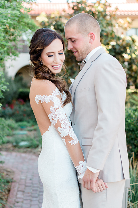 Temecula outdoor wedding at ponte winery bride form fitting lace gown with long sleeves and illusion open back design with sweetheart neckline and groom tan suit with matching vest and white dress shirt with matching tan bow tie and white floral boutonniere holding hands