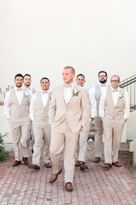 Temecula outdoor wedding at ponte winery groom tan suit with matching vest and white dress shirt with matching tan bow tie with white floral boutonniere with groomsmen tan suits with matching tan vests and tan bow ties walking