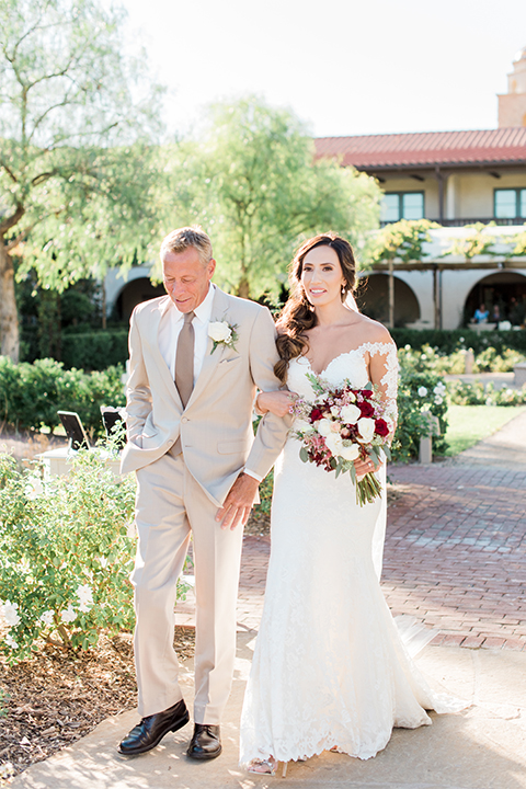 Temecula outdoor wedding at ponte winery bride form fitting lace gown with long sleeves and illusion open back design with sweetheart neckline holding white and red floral bridal bouquet walking down the aisle with dad tan suit with long brown tie