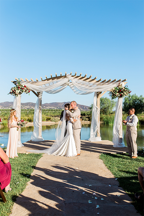 Temecula outdoor wedding at ponte winery bride form fitting lace gown with long sleeves and illusion open back design with sweetheart neckline and groom tan suit with matching vest and white dress shirt with matching tan bow tie and white floral boutonniere kissing during ceremony