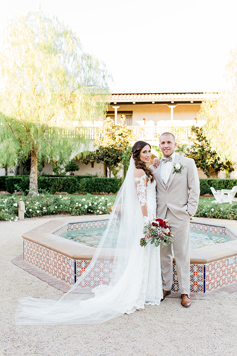 Temecula outdoor wedding at ponte winery bride form fitting lace gown with long sleeves and illusion open back design with sweetheart neckline and groom tan suit with matching vest and white dress shirt with matching tan bow tie and white floral boutonniere standing by fountain bride holding white and red floral bridal bouquet